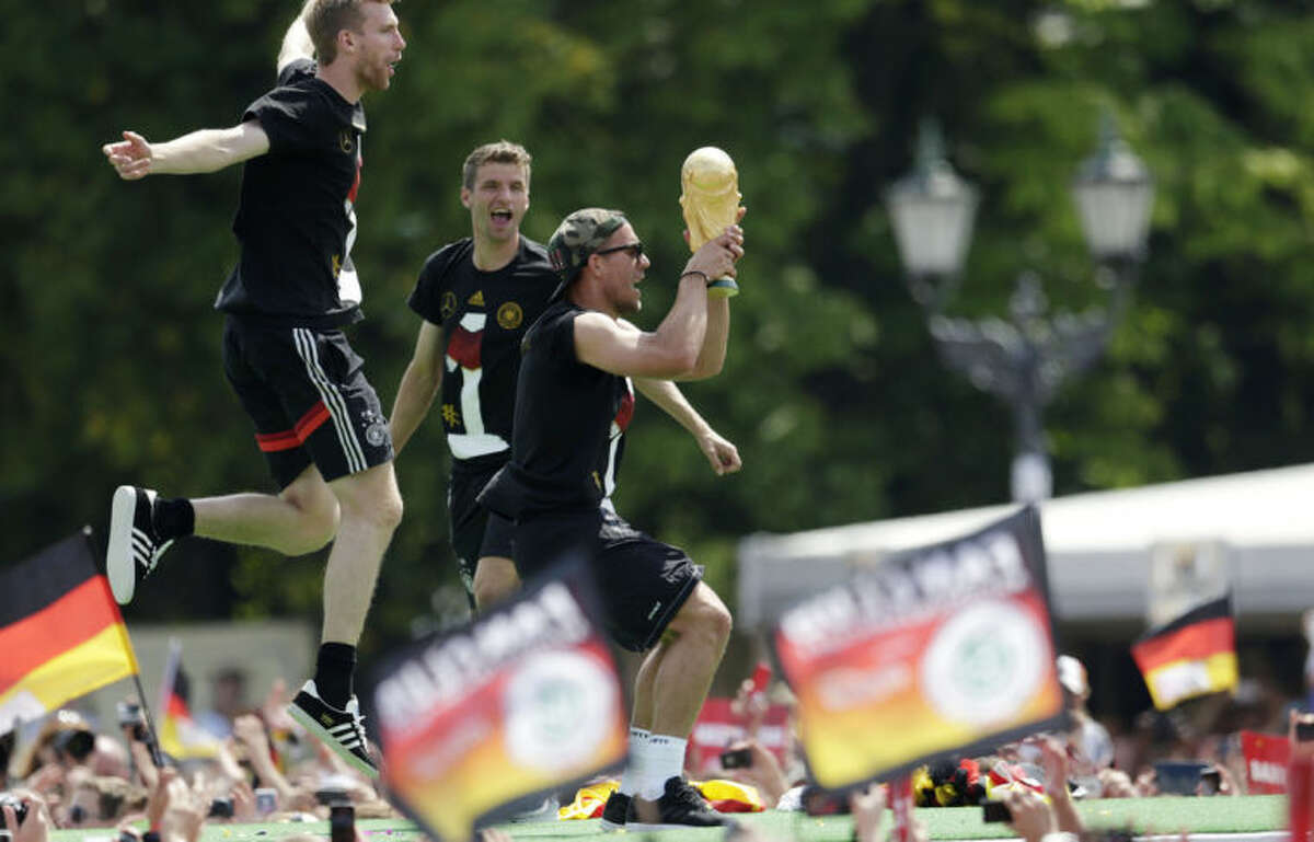Lukas Podolski holds the trophy during a fan party after the arrival of the German national soccer team in Berlin Tuesday, July 15, 2014. Germany beat Argentina 1-0 on Sunday to win its fourth World Cup title. (AP Photo/Petr David Josek)