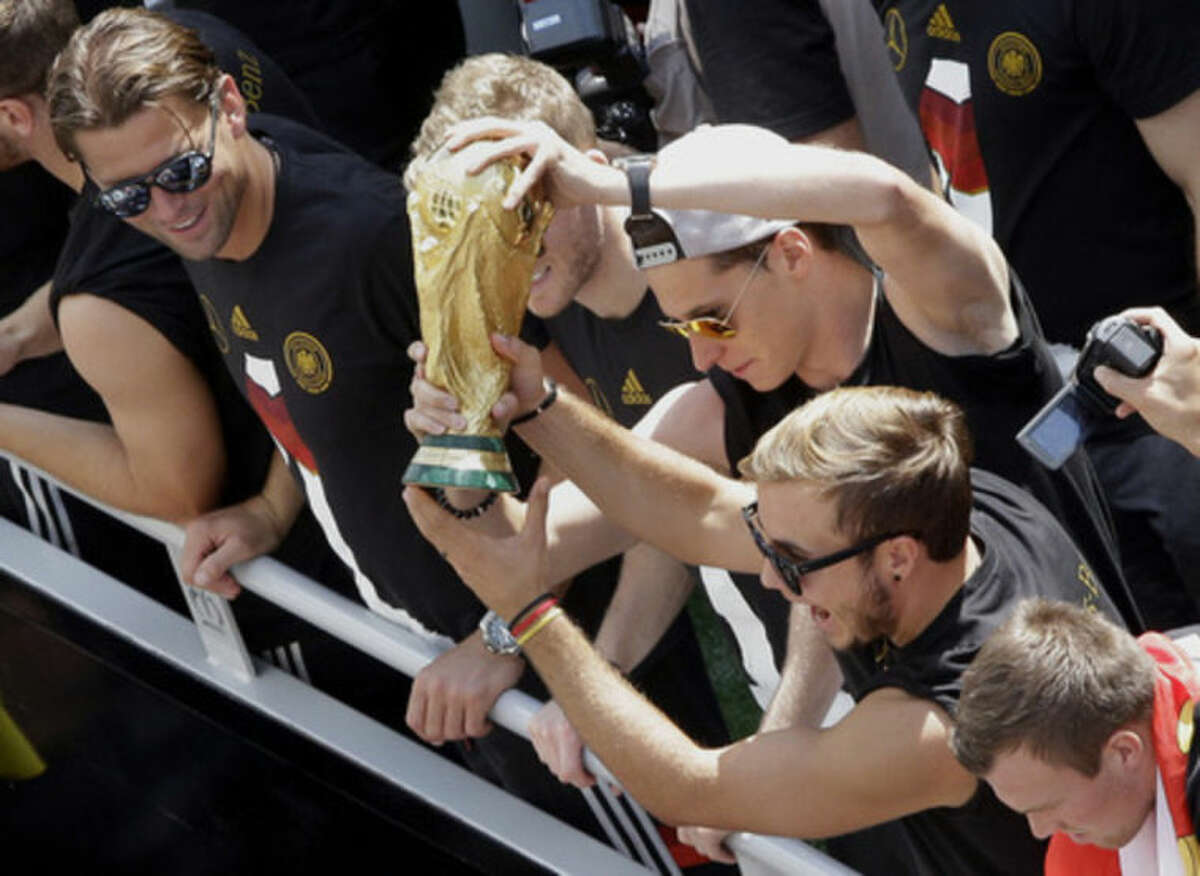 German soccer players Mario Goetze, right, and Julian Draxler , center, hold the trophy while goalie Roman Weidenfeller , left, looks on, after the arrival of the German national soccer squad in Berlin Tuesday, July 15, 2014. Germany?'s World Cup-winning team has returned home from Brazil to celebrate the country?'s fourth title with huge crowds of fans. The team?'s Boeing 747 touched down at Berlin?'s Tegel airport midmorning Tuesday after flying a lap of honor over the ?
