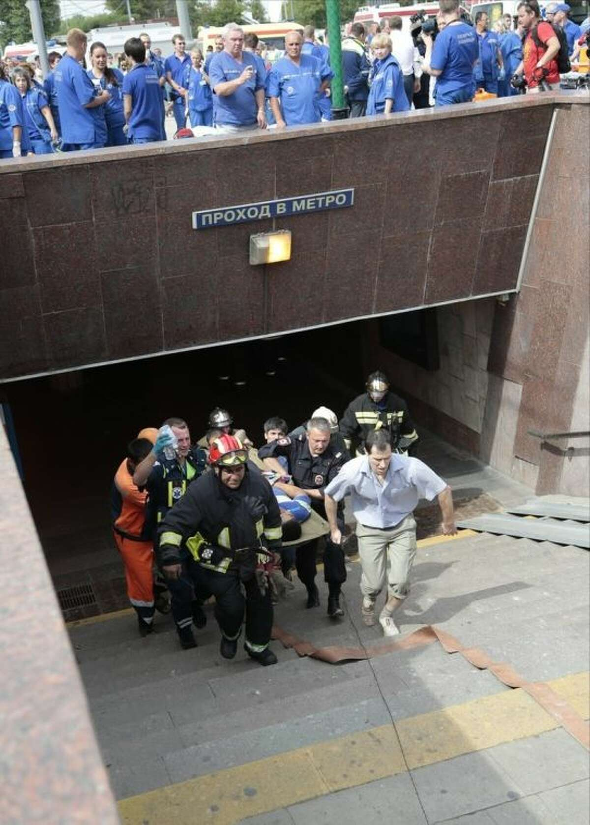 Paramedics, a police officer and a voluenteer carry an injured man out from a subway station after a rush-hour subway train derailment in Moscow, Russia, on Tuesday, July 15, 2014. A rush-hour subway train derailed in Moscow Tuesday, killing about a dozen people and injuring at least 106, emergency officials said. Several cars left the track in the tunnel after a power surge triggered an alarm, which caused the train to stop abruptly. (AP Photo/Ivan Sekretarev)