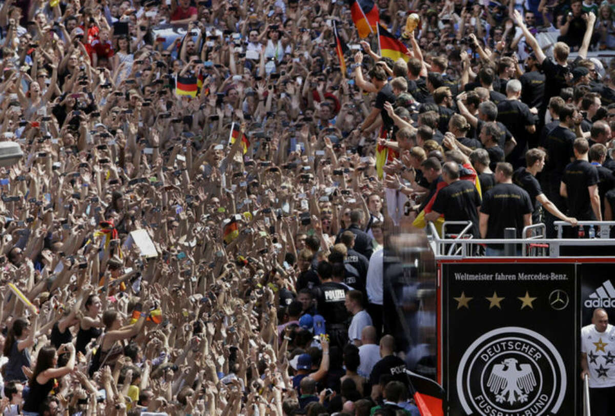 Members of the German soccer squad wave to fans after the arrival of the German national soccer team in Berlin Tuesday, July 15, 2014. Germany?'s World Cup-winning team has returned home from Brazil to celebrate the country?'s fourth title with huge crowds of fans. The team?'s Boeing 747 touched down at Berlin?'s Tegel airport midmorning Tuesday after flying a lap of honor over the ?