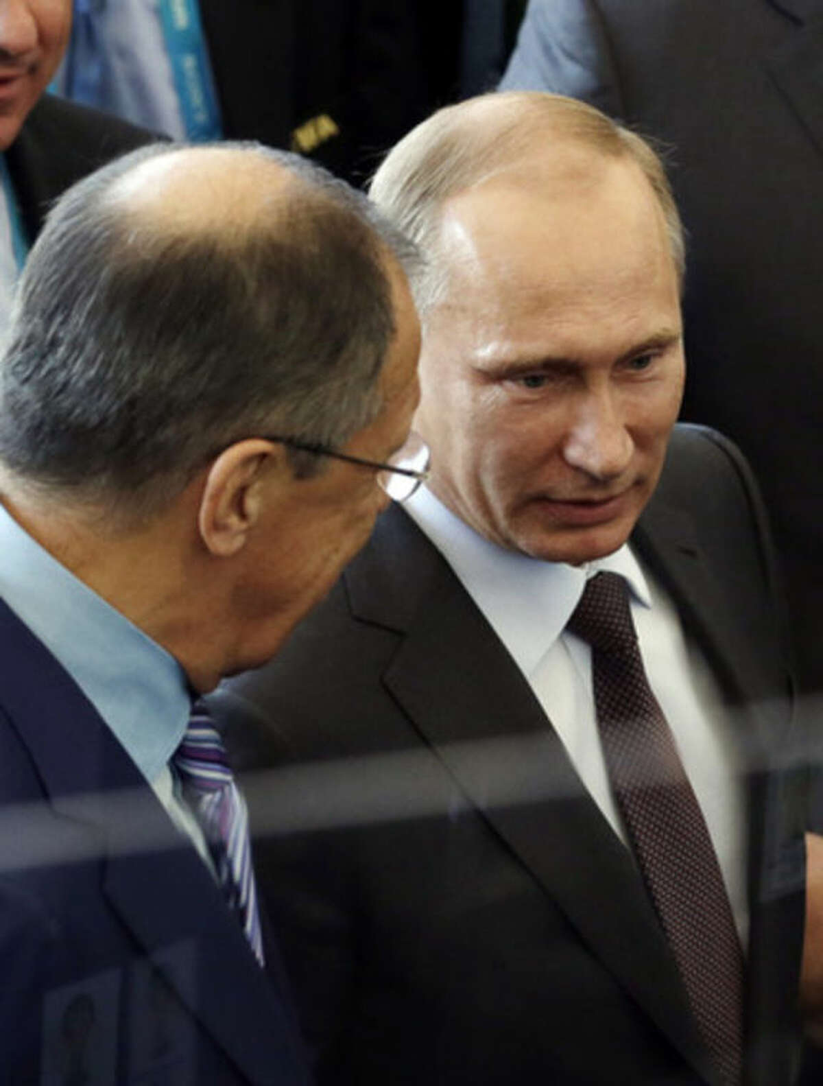 Russia's President Vladimir Putin talks to Russian Foreign Minister Sergei Lavrov during the World Cup final soccer match between Germany and Argentina at the Maracana Stadium in Rio de Janeiro, Brazil, Sunday, July 13, 2014. (AP Photo/Hassan Ammar)