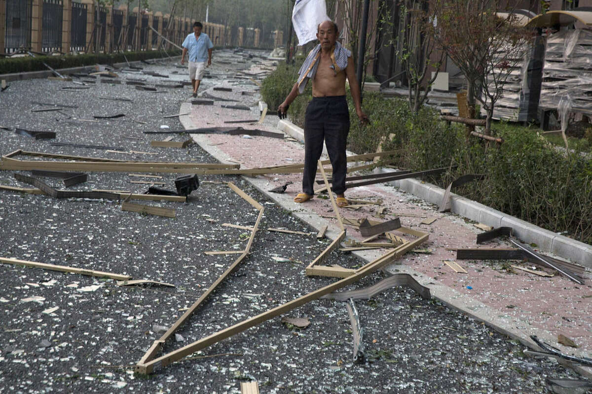 A man stands near broken glasses after a nearby explosion shattered windows at a residential compound, in China's Tianjin municipality, Thursday, Aug. 13, 2015. Huge explosions sparked overnight at a warehouse for dangerous materials in the northeastern Chinese port of Tianjin killed at least 13 people, injured hundreds and sent massive fireballs into the night sky, officials and state media outlets said Thursday. (AP Photo/Ng Han Guan)