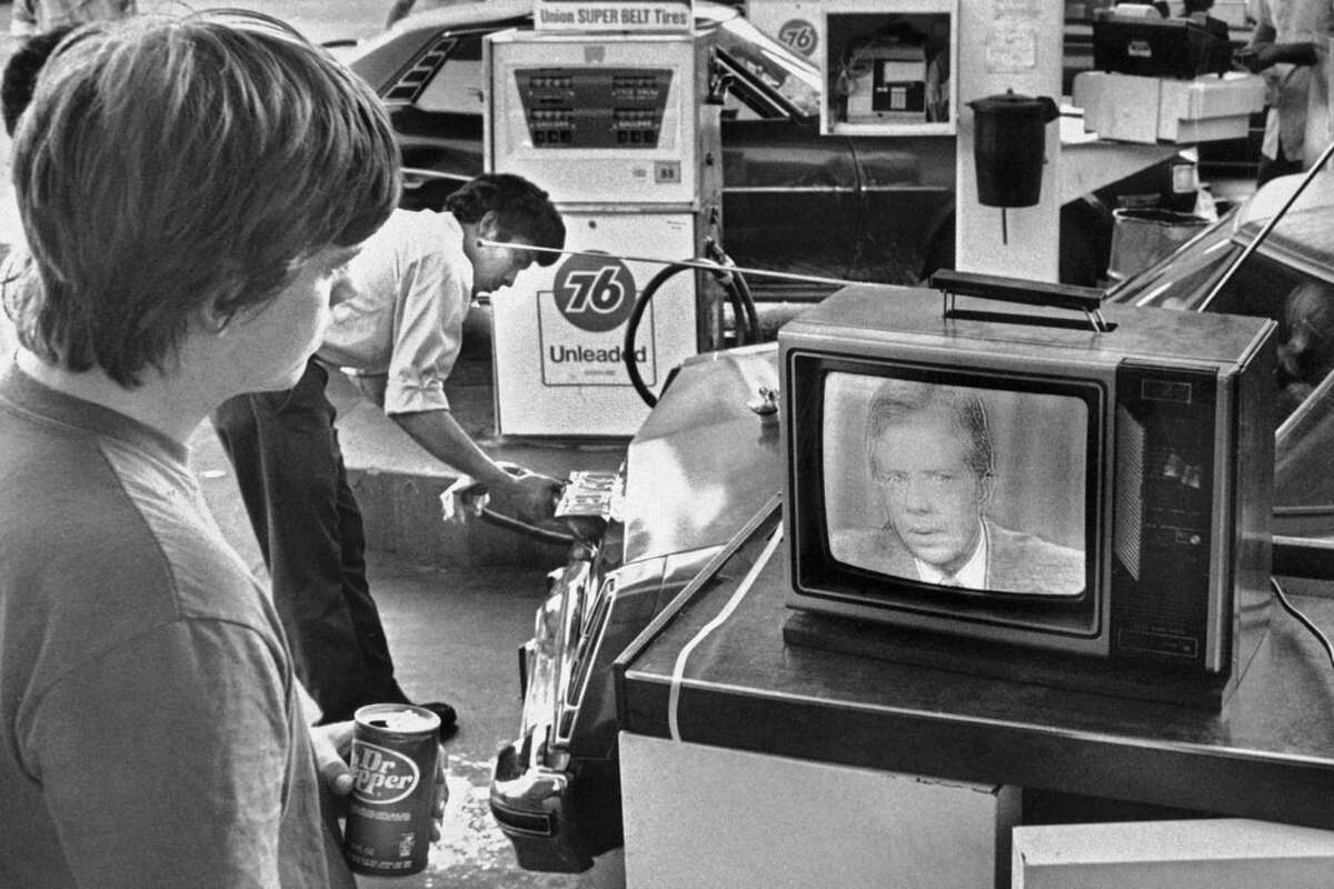 FILE - In this July 15, 1979 file photo, college student Chuck McManis watches President Jimmy Carter's nationally televised energy speech from a service station in Los Angeles, as a gas station attendant fills up a customer's car. On Wednesday, Aug. 12, 2015, Carter announced he has cancer and will undergo treatment at an Atlanta hospital. (AP Photo/Mao, File)
