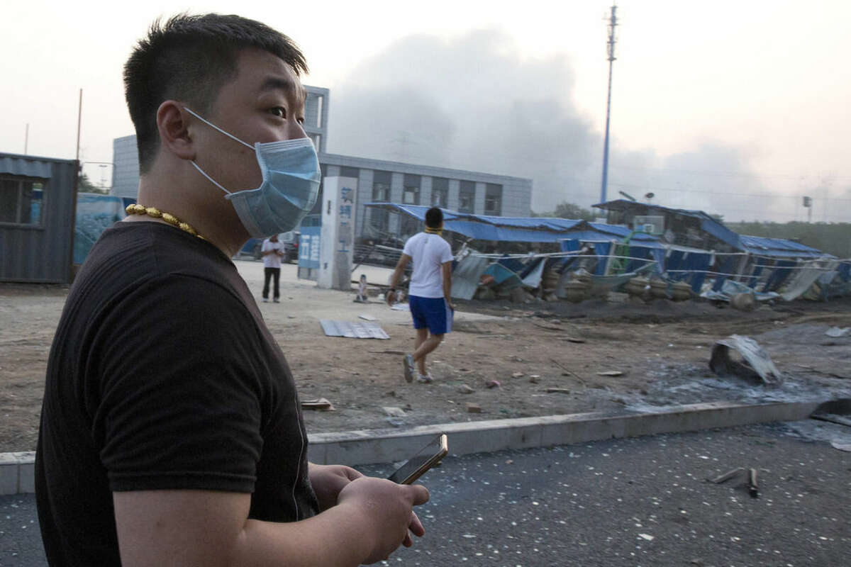 A man wears a mask as he visits an area damaged by an explosion in northeastern China's Tianjin municipality, Thursday, Aug. 13, 2015. Chinese state media reported huge explosions at the Tianjin port late Wednesday. (AP Photo/Ng Han Guan)