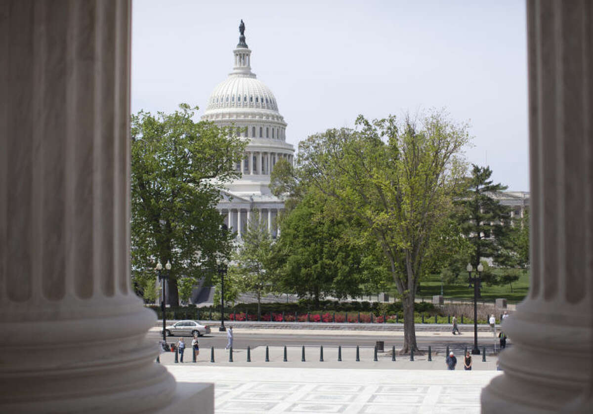 FILE - In this May 5, 2014, file photo, the U.S. Capitol building is seen through the columns on the steps of the Supreme Court in Washington. The House is poised to act on a bill that would temporarily patch over a multibillion-dollar pothole in federal highway and transit programs while ducking the issue of how to put the programs on sound financial footing for the long term. The bill by House Ways and Means Committee Chairman Dave Camp cobbles together $10.8 billion in pension tax changes, customs fees and money from a fund to repair leaking underground fuel storage tanks to keep the federal Highway Trust Fund solvent through May 2015. A similar bill is pending in the Senate. (AP Photo/Carolyn Kaster, File)