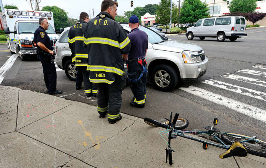 Hour photo / Erik Trautmann Emergency personnel respond to 100 Westport Ave where a bicyclist was struck by a motor vehicle shortly after eight Tuesday monring.