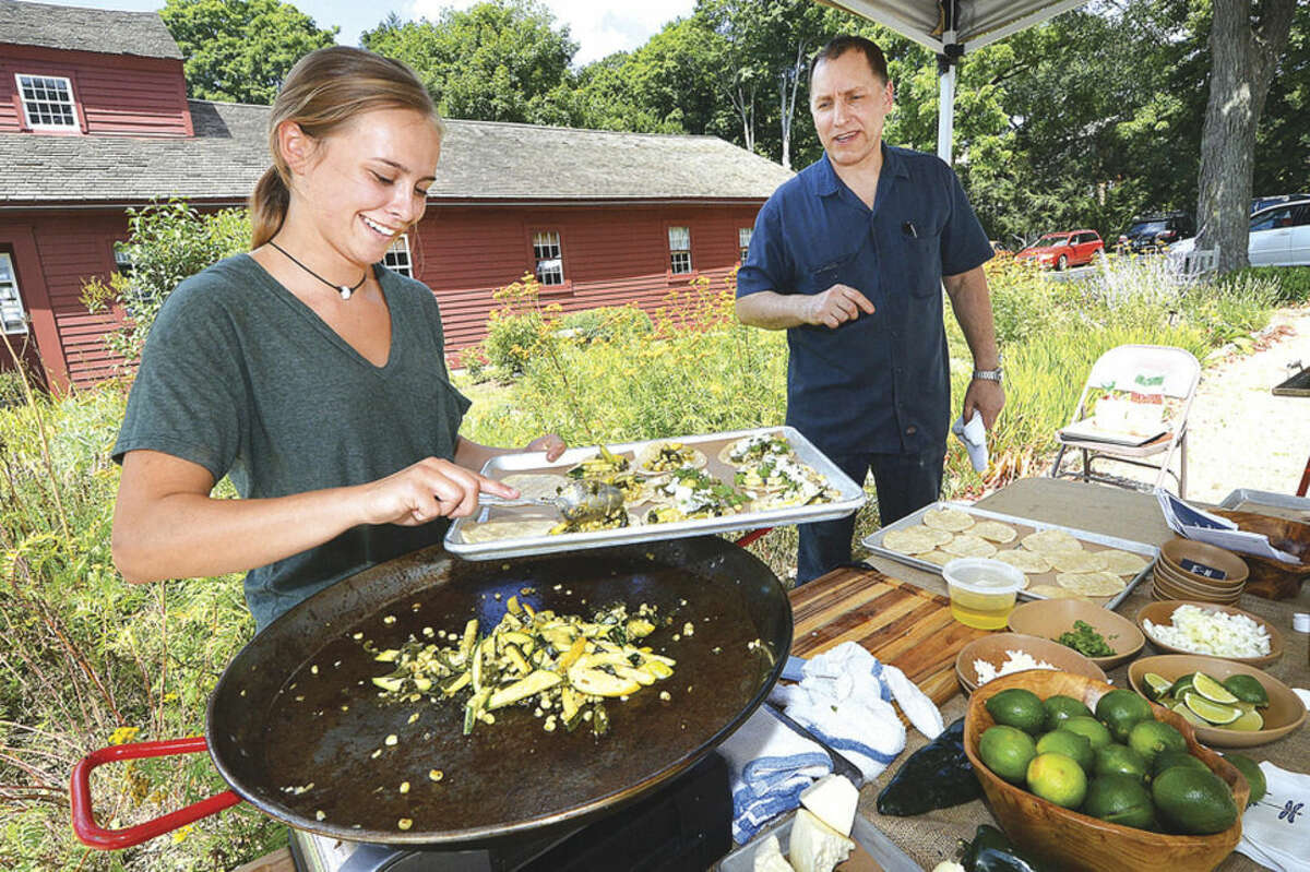 Hour Photo/Alex von Kleydorff Bar Taco Sous Chef Carly Lenihan and Executive Chef Mike Hazen make up a fresh batch of Wilton Farmers Market Tacos, made from ingredients available at the market during a chef demonstration on Wednesday.