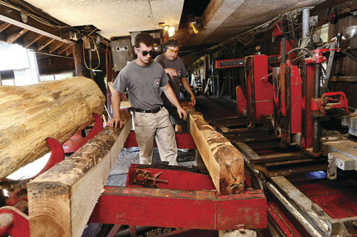 Phoo by Erik Trautmann Employee Carl Strate and Taber Gregory, owner of Gregory Sawmill in Wilton which has been in his family for over 100 years, ready timber for cutting.