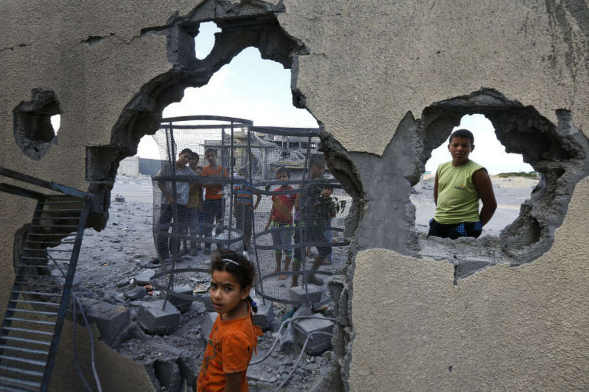 Palestinian Suma Abu Mahsen, 7, stands by a damaged wall of a house following an overnight Israeli missile strike to a nearby transition center for newly released convicts, that was not yet operational, in Rafah, southern Gaza Strip, Tuesday, July 15, 2014. An Egyptian truce proposal for the conflict in Gaza quickly unraveled Tuesday, after the Islamic militant group Hamas rejected the plan. (AP Photo/Lefteris Pitarakis)