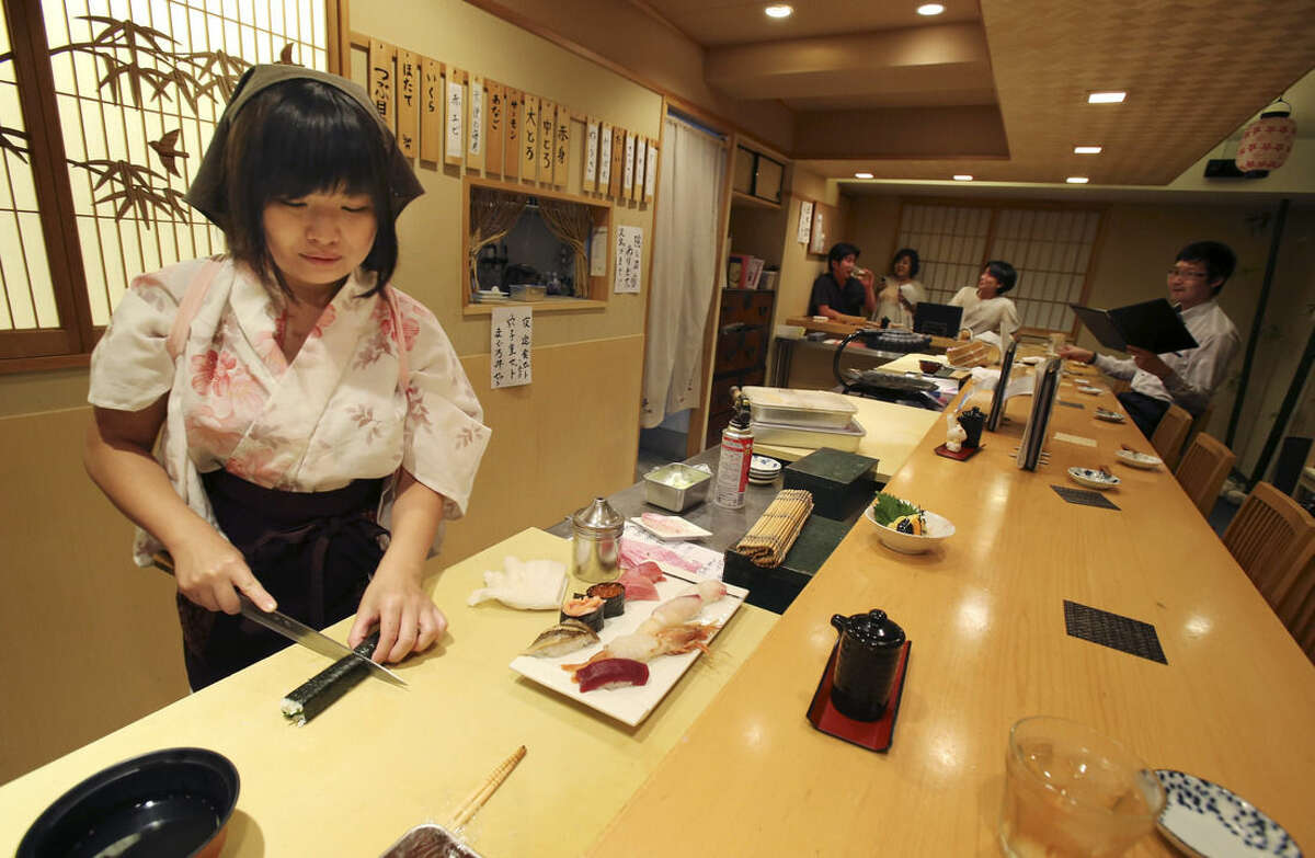 In this Aug. 3, 2015 photo, Yuki Chidui, sushi chef and manager at Nadeshico sushi restaurant, cuts a cucumber roll to make a set of sushi at her all-women restaurant in Tokyo. Deeply rooted stereotypes such as the so-called