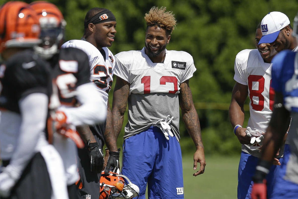 Cincinnati Bengals halfback Jeremy Hill, center left, and New York Giants wide receiver Odell Beckham Jr., center, laugh on the sidelines during a joint NFL football training camp, Wednesday, Aug. 12, 2015, in Cincinnati. (AP Photo/John Minchillo)