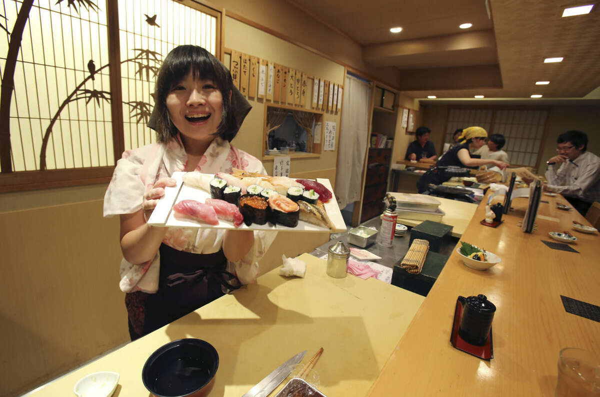 In this Aug. 3, 2015 photo, Yuki Chidui, sushi chef and manager at Nadeshico sushi restaurant, shows off a set of sushi she made at her all-women restaurant in Tokyo. Deeply rooted stereotypes such as the so-called
