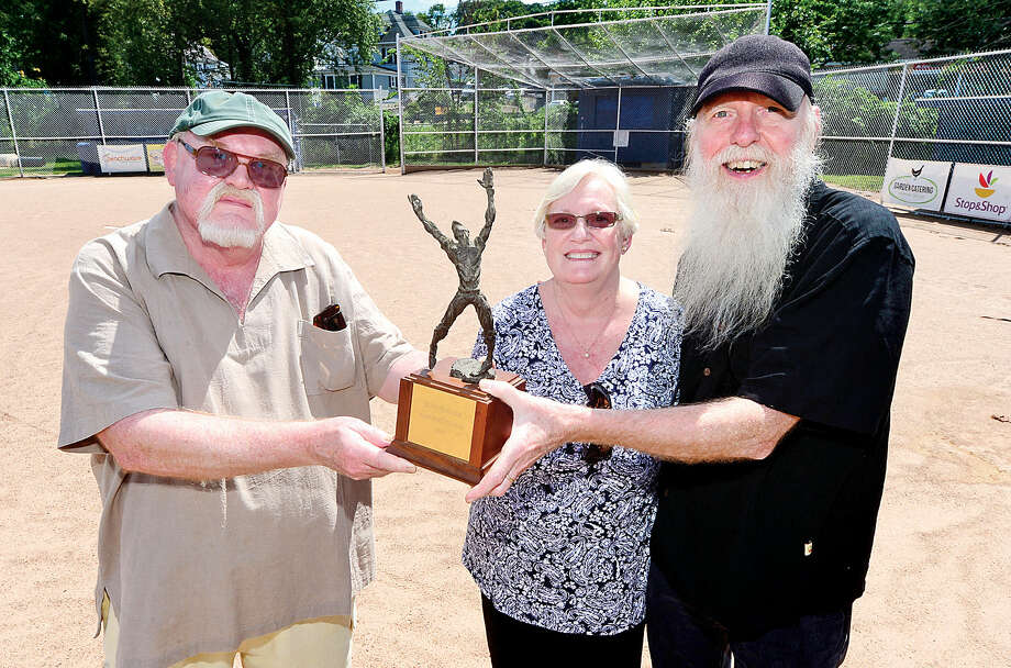 The older siblings of David Kinlock, (l-to-r) Einar, Karen and Ray Kinlock, hold the original David Kinlock Sportsmanship Award the International Little League created in 1971, a year after he lost his life in an accident. In 1975, the David Kinlock Memorial Tournament began. The championship game that first year was played at the Broad River Little League field the Kinlock siblings are standing on. (Hour photo/Erik Trautmann)