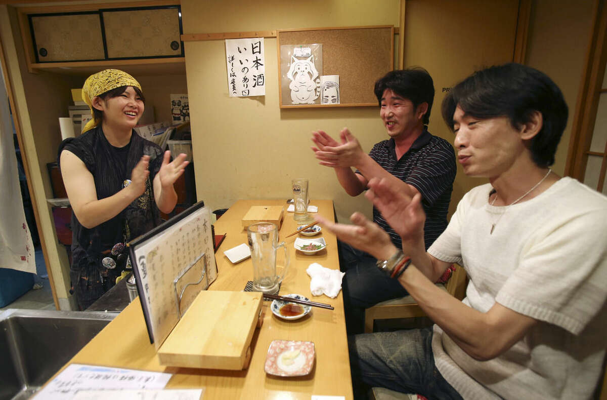 In this Aug. 3, 2015 photo, Ayaka Kurogi, 19, left, an employee of Nadeshico sushi restaurant, chats with customers Masataka Nakayama, center, and Yoichi Okuda over the counter at the all-women restaurant in Tokyo. Deeply rooted stereotypes such as the so-called