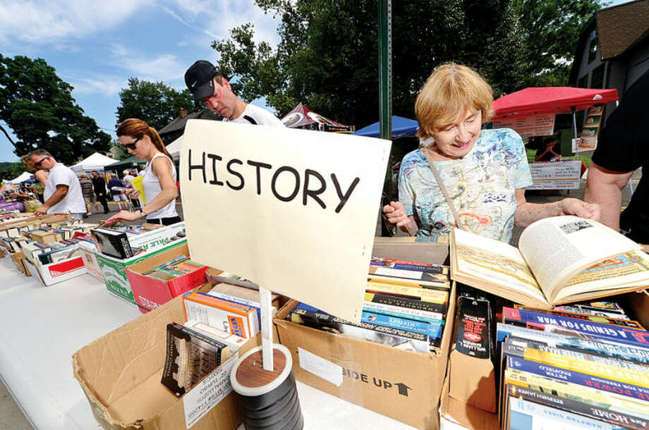 Hour photo / Erik Trautmann Carol Roberts looks over the offerings from the Wilton Public Library during the 3rd annual Wilton Street Fair and Sidewalk Sale in Wilton Center Saturday.