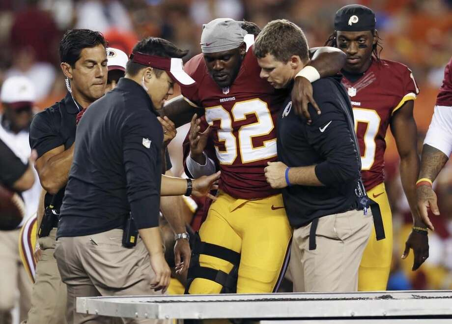 Norwalk's Silas Redd Jr. of the Washington Redskins is helped off the field and onto a cart after suffering a knee injury during Thursday night's NFL Preseason opener in Cleveland.