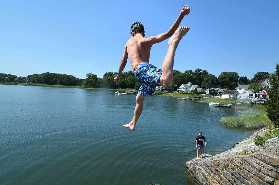 Hour Photo/Alex von Kleydorff 11yr old Phillip Stalzer takes a plunge into Farm Creek as the summer tradition for neighborhood kids to swim during High Tide off the bridge to Bell Island