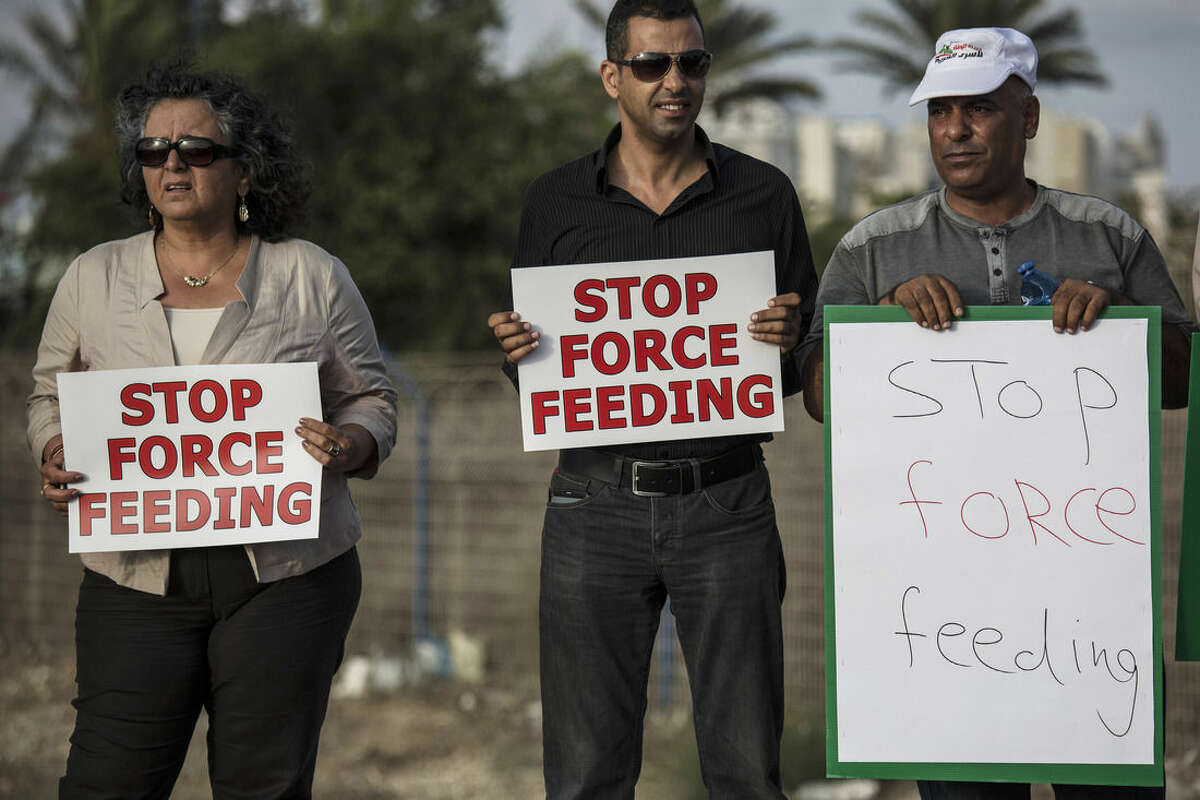 In this photo made on Tuesday, August 11, 2015, Israeli Arab supporters of Mohammed Allan, a Palestinian prisoner on a hunger strike, hold signs during a support rally outside Barzilai hospital, in the costal city of Ashkelon Israel. Israel passed a law to force feed hunger strikers by a slim margin in July and elicited harsh criticism. Critics call force-feeding an unethical violation of patient autonomy and akin to torture. The Israeli Medical Association, which has urged physicians not to cooperate, is challenging the law in the Supreme Court. (AP Photo/Tsafrir Abayov)