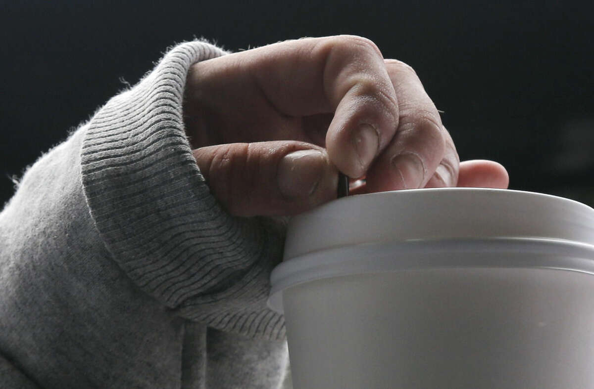 In this July 10, 2015, photo, a woman squeezes her coffee stirrer as she speaks to The Associated Press in Gloucester, Mass. The woman voluntarily came to the police for help kicking her heroin addiction. Gloucester is taking a novel approach to the war on drugs, making the police station a first stop for addicts on the road to recovery. Addicts can turn in their drugs to police, no questions asked, and officers, volunteers and trained clinicians help connect them with detox and treatment services. (AP Photo/Elise Amendola)