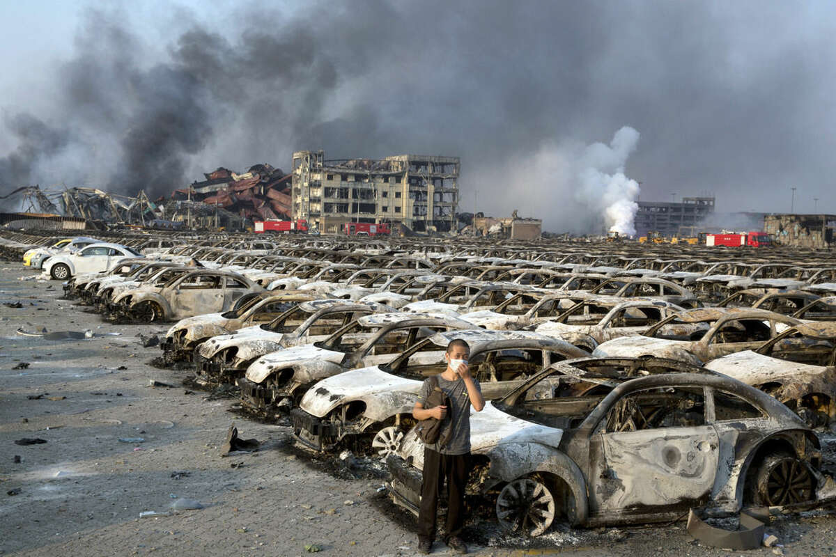 In this photo taken Thursday, Aug. 13, 2015, a man stands near the charred remains of new cars at a parking lot near the site of an explosion at a warehouse in northeastern China's Tianjin municipality. Rescuers have pulled a survivor from an industrial zone about 32 hours after it was devastated by huge blasts in China's Tianjin port. Meanwhile, authorities are moving gingerly forward in dealing with a fire still smoldering amid potentially dangerous chemicals. (AP Photo/Ng Han Guan)