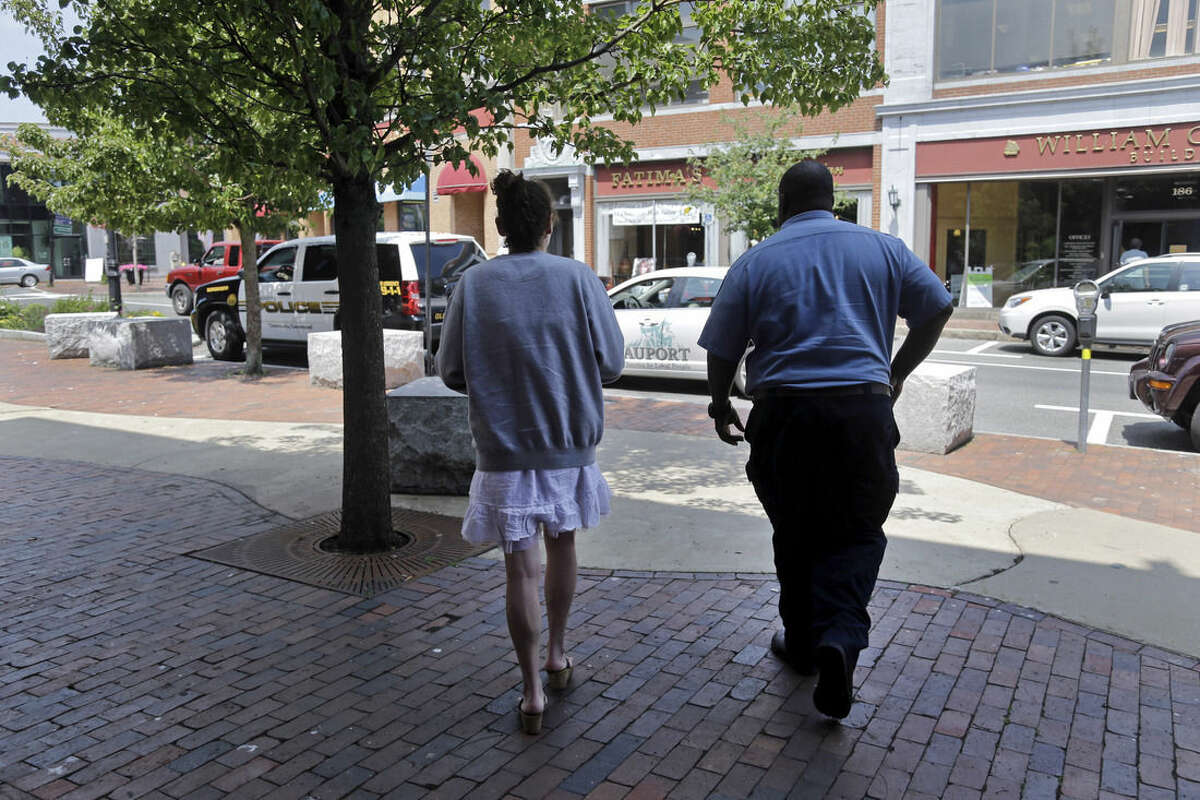 In this July 10, 2015, photo, a woman walks from the police station in Gloucester, Mass., for her ride to an area detox facility. The woman voluntarily came to the police for help kicking her heroin addiction. Gloucester is taking a novel approach to the war on drugs, making the police station a first stop for addicts on the road to recovery. Addicts can turn in their drugs to police, no questions asked, and officers, volunteers and trained clinicians help connect them with detox and treatment services. (AP Photo/Elise Amendola)