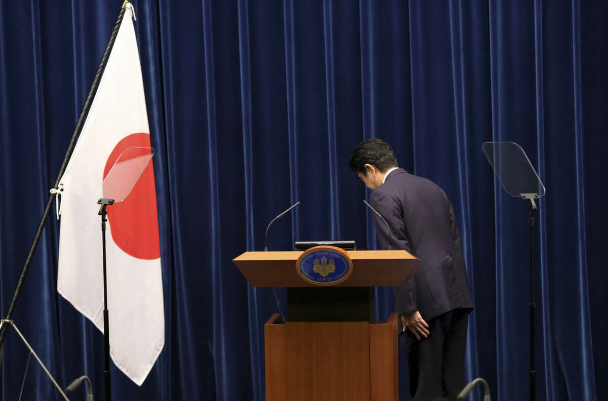 Japanese Prime Minister Shinzo Abe bows to the Japanese flag before delivering a statement to mark the 70th anniversary of the end of World War II during a press conference at his official residence in Tokyo Friday, Aug. 14, 2015. Abe has expressed