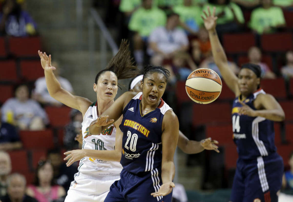 Connecticut Sun's Alex Bentley (20) reaches for the ball after it was tipped away by Seattle Storm's Sue Bird in the first half of a WNBA basketball game as Sun's Kelsey Bone calls for the ball behind Tuesday, July 15, 2014, in Seattle. (AP Photo/Elaine Thompson)