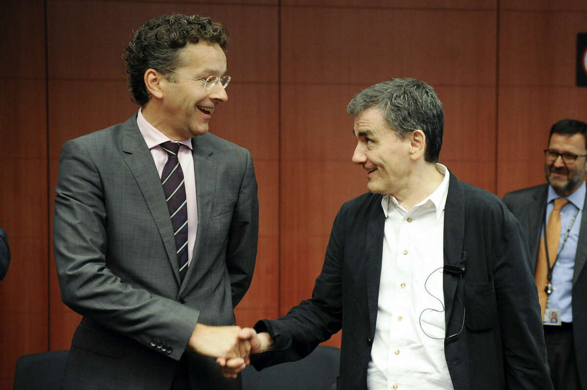 Dutch Finance Minister and chairman of the eurogroup Jeroen Dijsselbloem, left, shakes hands with Greek Finance Minister Euclid Tsakalotos during a meeting of eurozone finance ministers at the EU Council building in Brussels on Friday, Aug. 14, 2015. (AP Photo/Laurent Dubrule)