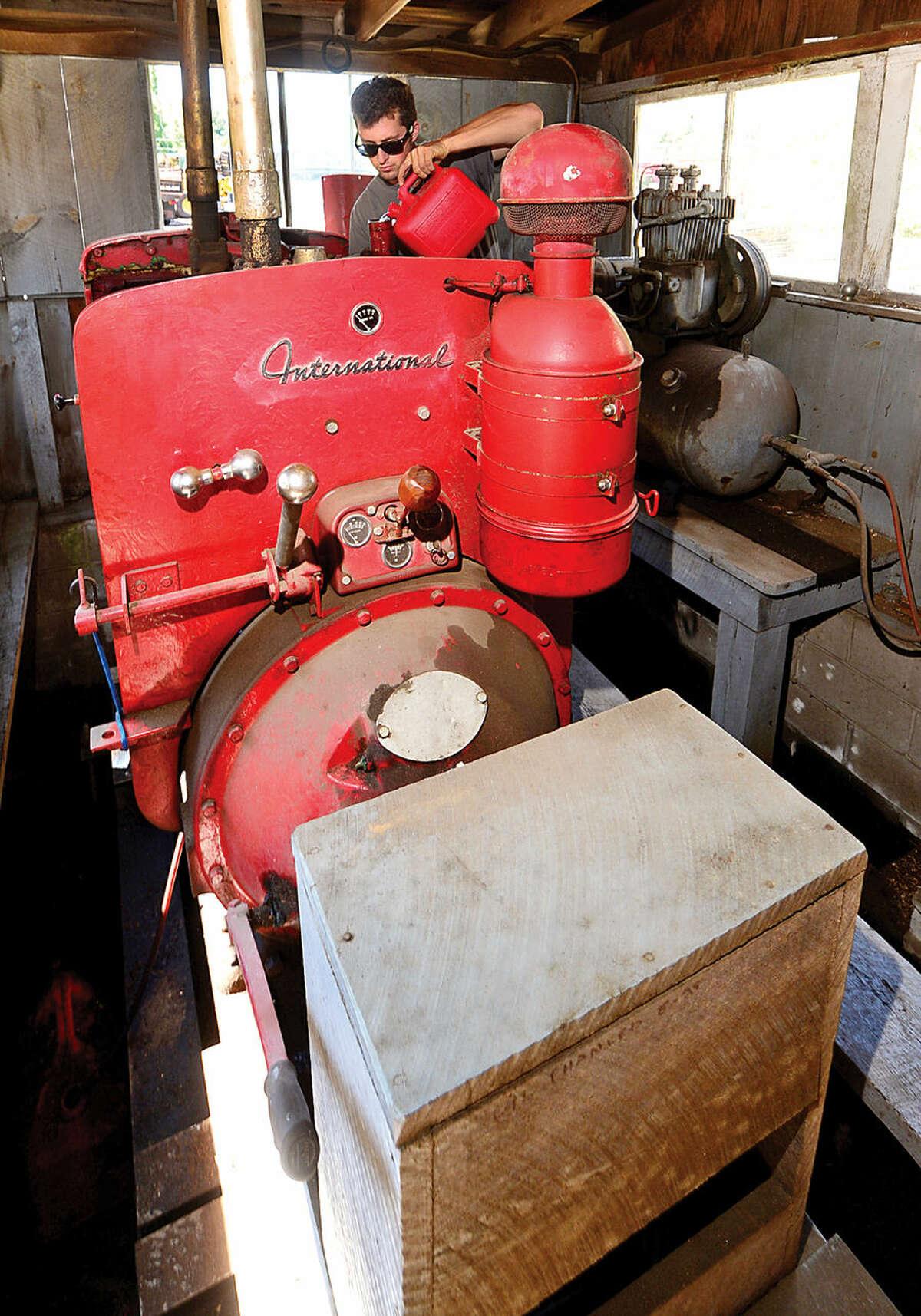 Hour photo / Erik Trautmann Gregory Sawmill employee Carl Strate readies the saw generator,