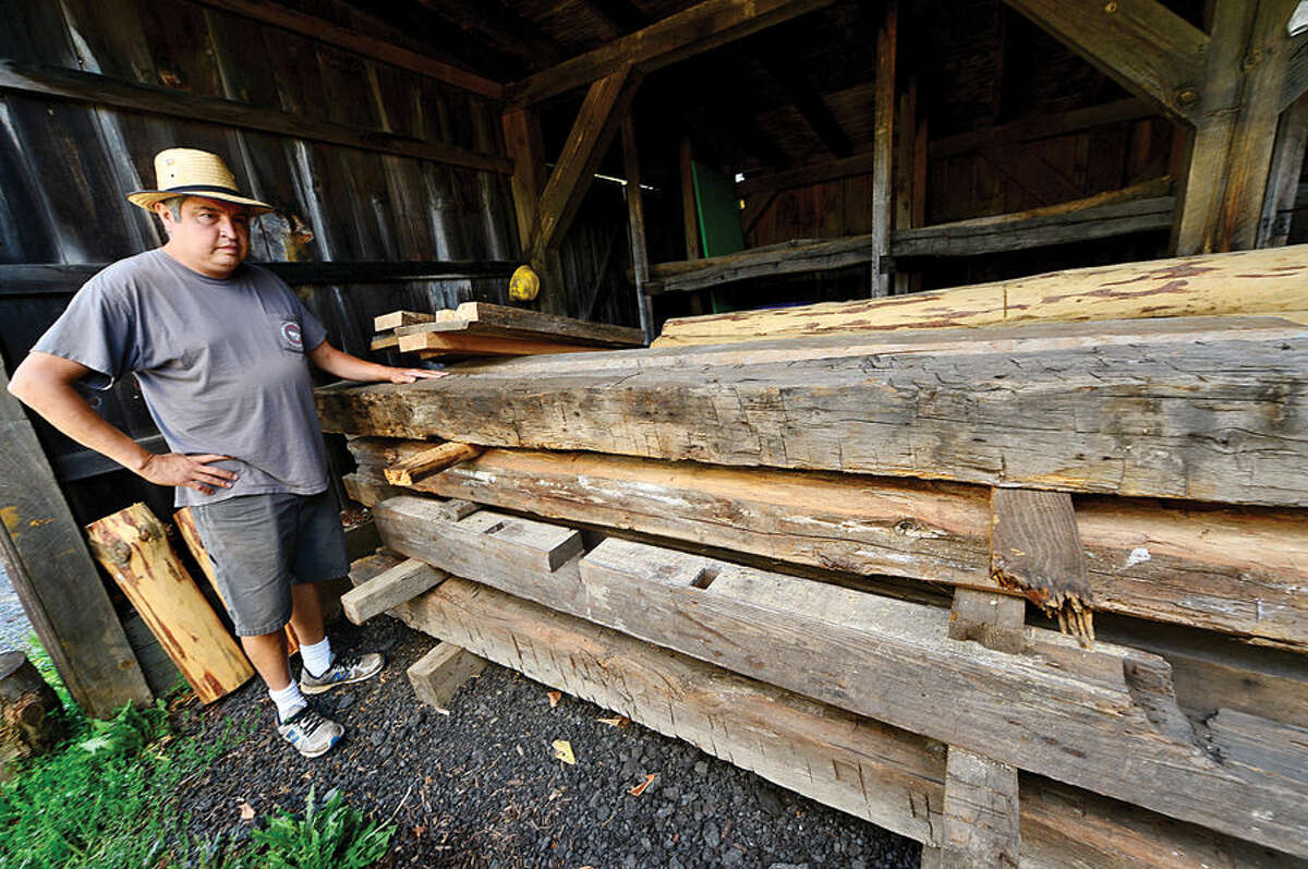 Hour photo / Erik Trautmann Taber Gregory, owner of Gregory Sawmill in Wilton which has been in his family for over 100 years, displays some of the antique lumber.