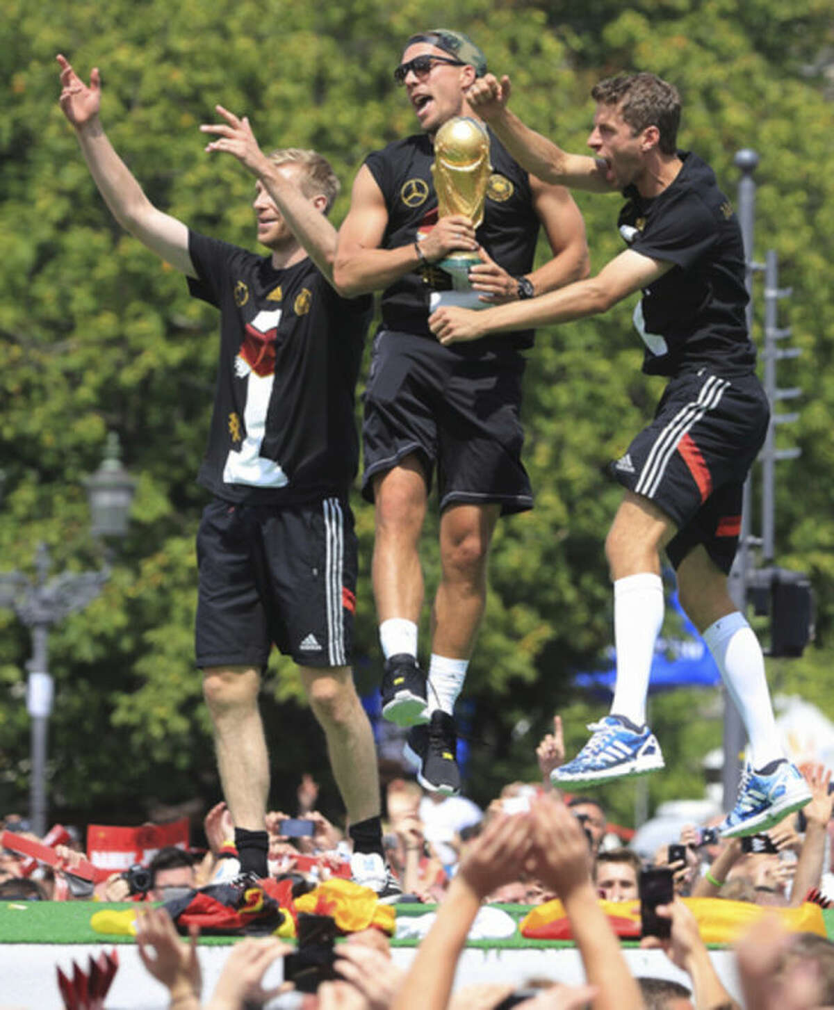 German national soccer players from left: Per Mertesacker , Lukas Podolski and Thomas Mueller celebrate near Brandenburg Gate in Berlin, Tuesday July 15, 2014. Germany's World Cup winners shared their fourth title with hundreds of thousands of fans by parading the trophy through cheering throngs to celebrate at the Brandenburg Gate on Tuesday. An estimated 400,000 people packed the