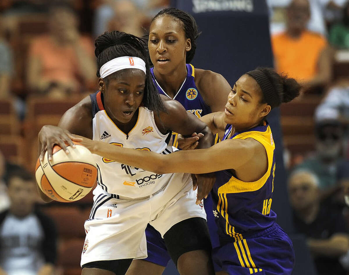 Connecticut Sun?'s Chiney Ogwumike, left, is pressured by Los Angeles Sparks?' Sandrine Gruda, back center, and Lindsey Harding, right, during the first half of a WNBA basketball game, Sunday, July 13, 2014, in Uncasville, Conn. The Sparks won 90-64. (AP Photo/Jessica Hill)