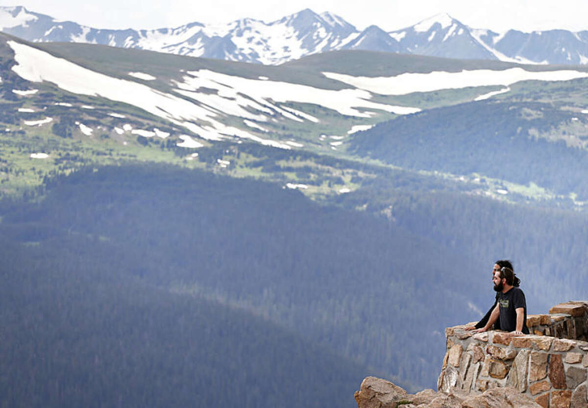 Two men take in a scenic overlook off Trail Ridge Road at Rocky Mountain National Park, west of Estes Park, Colo., Monday, July 14, 2014. Lightning killed two people last weekend just miles apart in the popular park, where summer storms can close in quickly with deadly results. (AP Photo/Brennan Linsley)