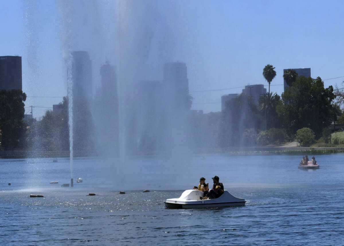 Visitors in a paddle boat cool themselves under a large fountain in Echo Park Lake near downtown Los Angeles on Friday, Aug. 14, 2015. The National Weather Service says Southern California's sharp warming trend will build into the weekend, with above-normal temperatures in many areas. Forecasters say the hottest conditions will be Friday through Sunday. Valley and desert temperatures will range from 100 to108 degrees, with highs from 85 to 95 elsewhere. (AP Photo/Richard Vogel)