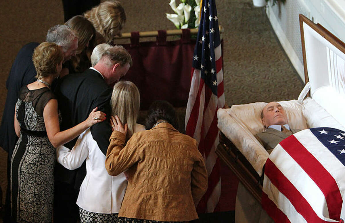 The family of former U.S. Sen. Alan Dixon pauses at his casket before it is closed during his funeral Monday July 14, 2014, at Lindenwood University in Belleville, Ill. Dixon was eulogized by his son and former colleagues as a devoted public servant savvy about brokering deals and unwilling to compromise his principles. (AP Photo/Belleville News-Democrat, Steve Nagy)