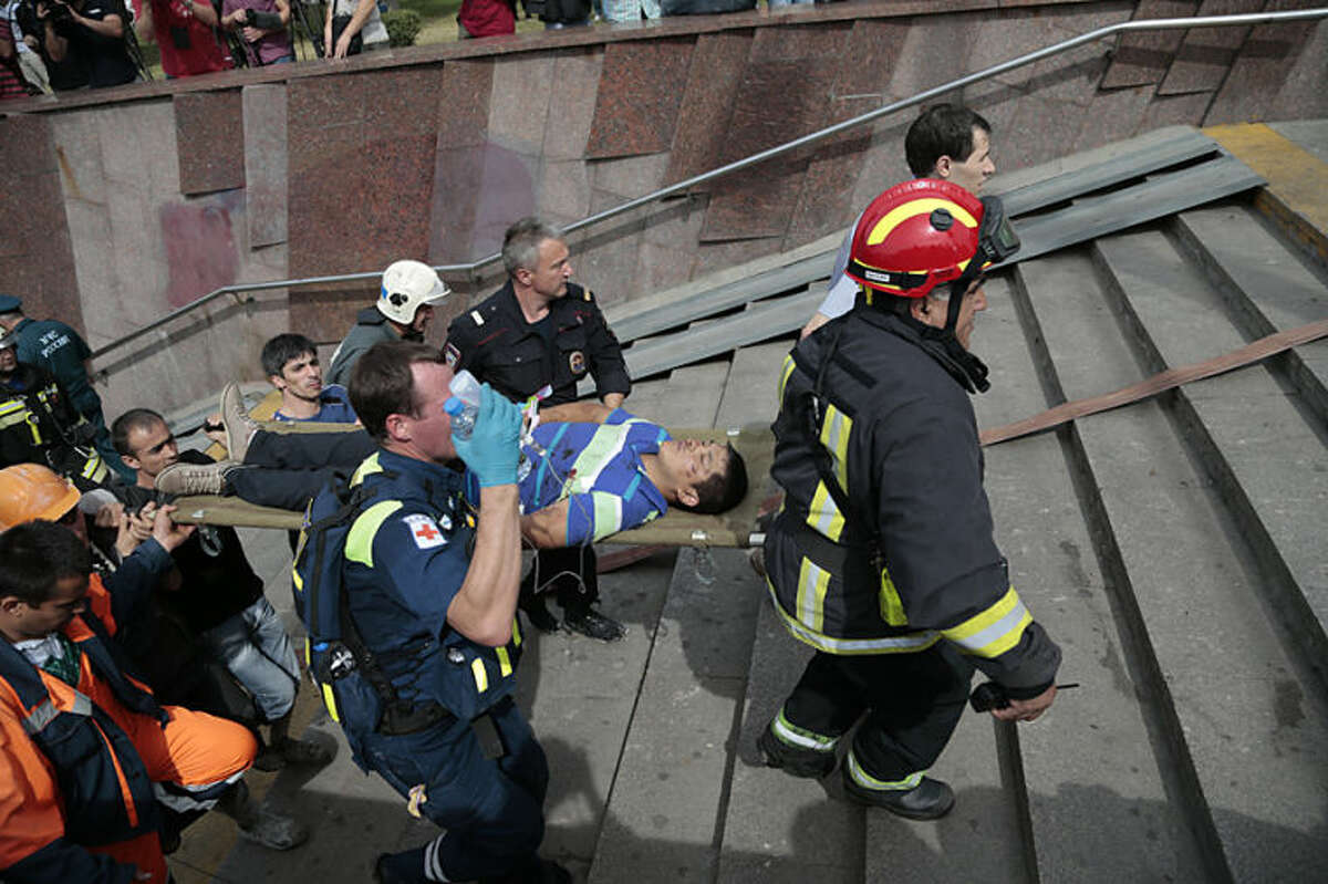 CAPTION CORRECTION REMOVES REFERENCE TO CAUSE OF DERAILMENT. THE CAUSE IS UNDER INVESTIGATION Paramedics, a police officer and a volunteer carry an injured man out from a subway station after a rush-hour subway train derailment in Moscow, Russia, on Tuesday, July 15, 2014. A rush-hour subway train derailed in Moscow Tuesday, killing more than 20 people and injuring scores, emergency officials said. The cause of the derailment is being investigated. (AP Photo/Ivan Sekretarev)