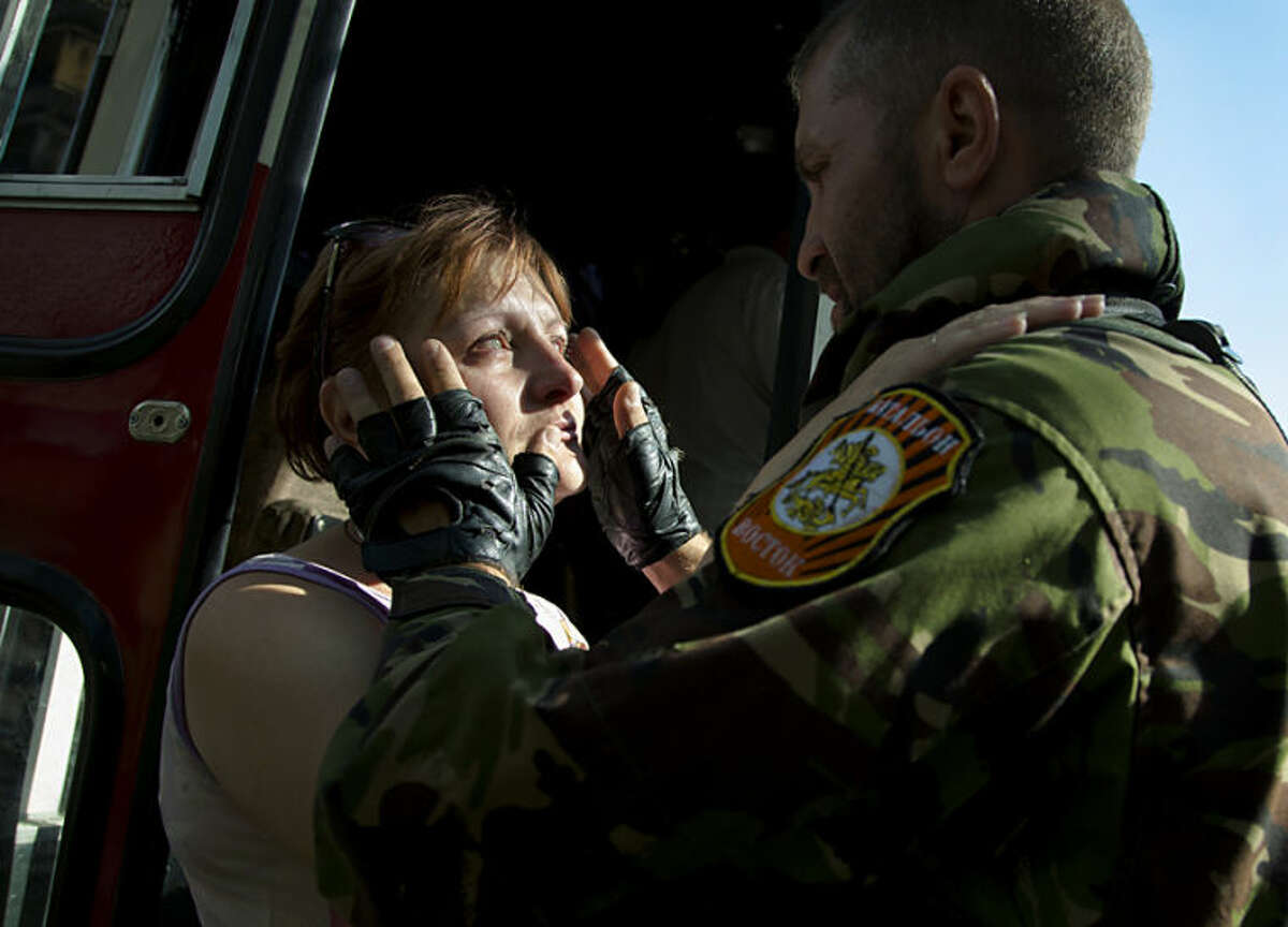 A Donetsk People's Republic fighter, name not given, says goodbye to his wife departing as a refugee to Russia in the city of Donetsk, eastern Ukraine Wednesday, July 16, 2014. Ten busloads of Internally Displaced People from the towns of Karlovka, Maryinka and Donetsk left Wednesday morning for the Rostov region in Russia to ask for refugee status there. (AP Photo/Dmitry Lovetsky)