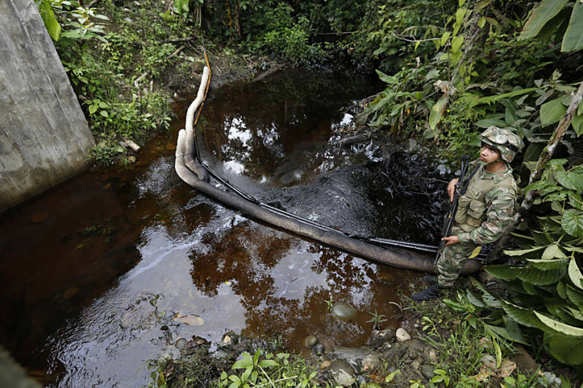 A soldier stands along a creek contaminated with crude oil in Puerto Asis, in Colombia's southwestern state of Putumayo, Tuesday, July 15, 2014. Authorities are trying to control an oil spill that, according to the Minister of Mining, Amylkar Acosta, was caused when rebels of the Revolutionary Armed Forces of Colombia, FARC, forced truck drivers to dump nearly four thousand barrels of crude when they intercepted a convoy of 19 trucks carrying oil near the border with Ecuador. (AP Photo/Fernando Vergara)