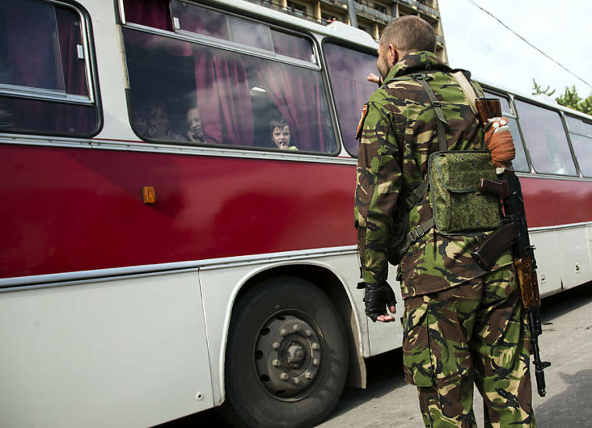 A Donetsk People's Republic fighter says goodbye to his family who are departing as refugees to Russia in the city of Donetsk, eastern Ukraine Wednesday, July 16, 2014. Ten busloads of Internally Displaced People from the towns of Karlovka, Maryinka and Donetsk left Wednesday morning for the Rostov region in Russia to ask for refugee status there. (AP Photo/Dmitry Lovetsky)