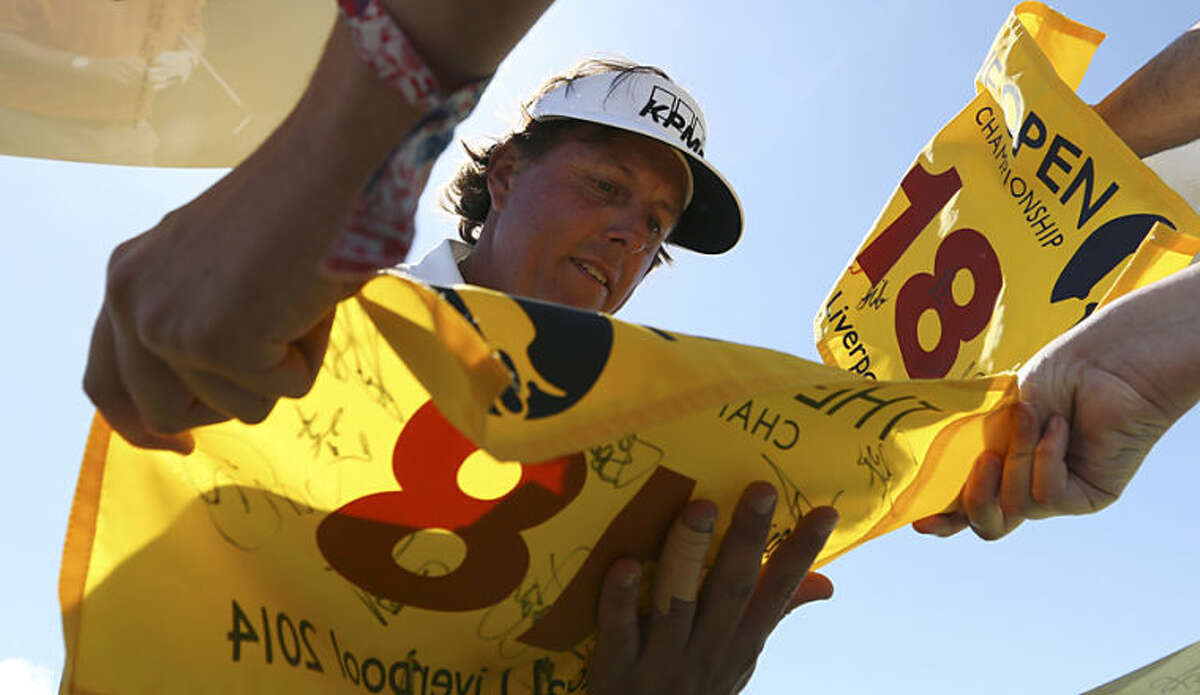 Phil Mickelson of the US signs autographs for fans after a practice round ahead of the British Open Golf championship at the Royal Liverpool golf club, Hoylake, England, Tuesday July 15, 2014. The British Open Golf championship starts on Thursday July 17. (AP Photo/Jon Super)