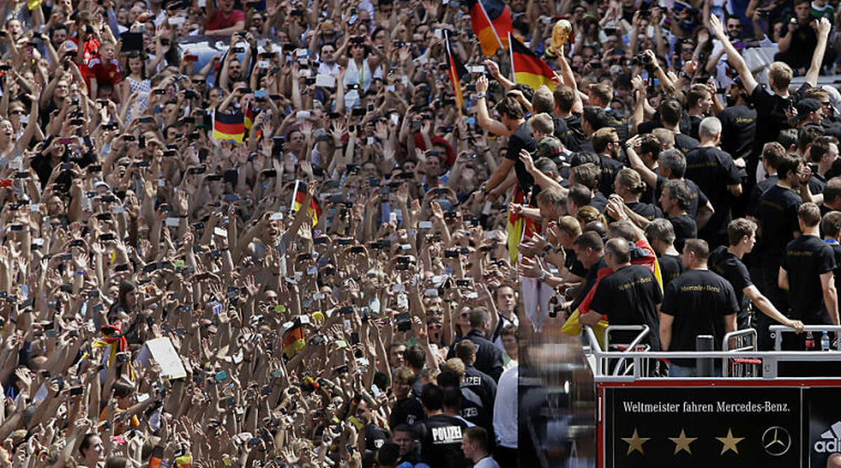 Members of the German soccer squad wave to fans after the arrival of the German national soccer team in Berlin Tuesday, July 15, 2014. Germany's World Cup-winning team has returned home from Brazil to celebrate the country's fourth title with huge crowds of fans. The team's Boeing 747 touched down at Berlin's Tegel airport midmorning Tuesday after flying a lap of honor over the