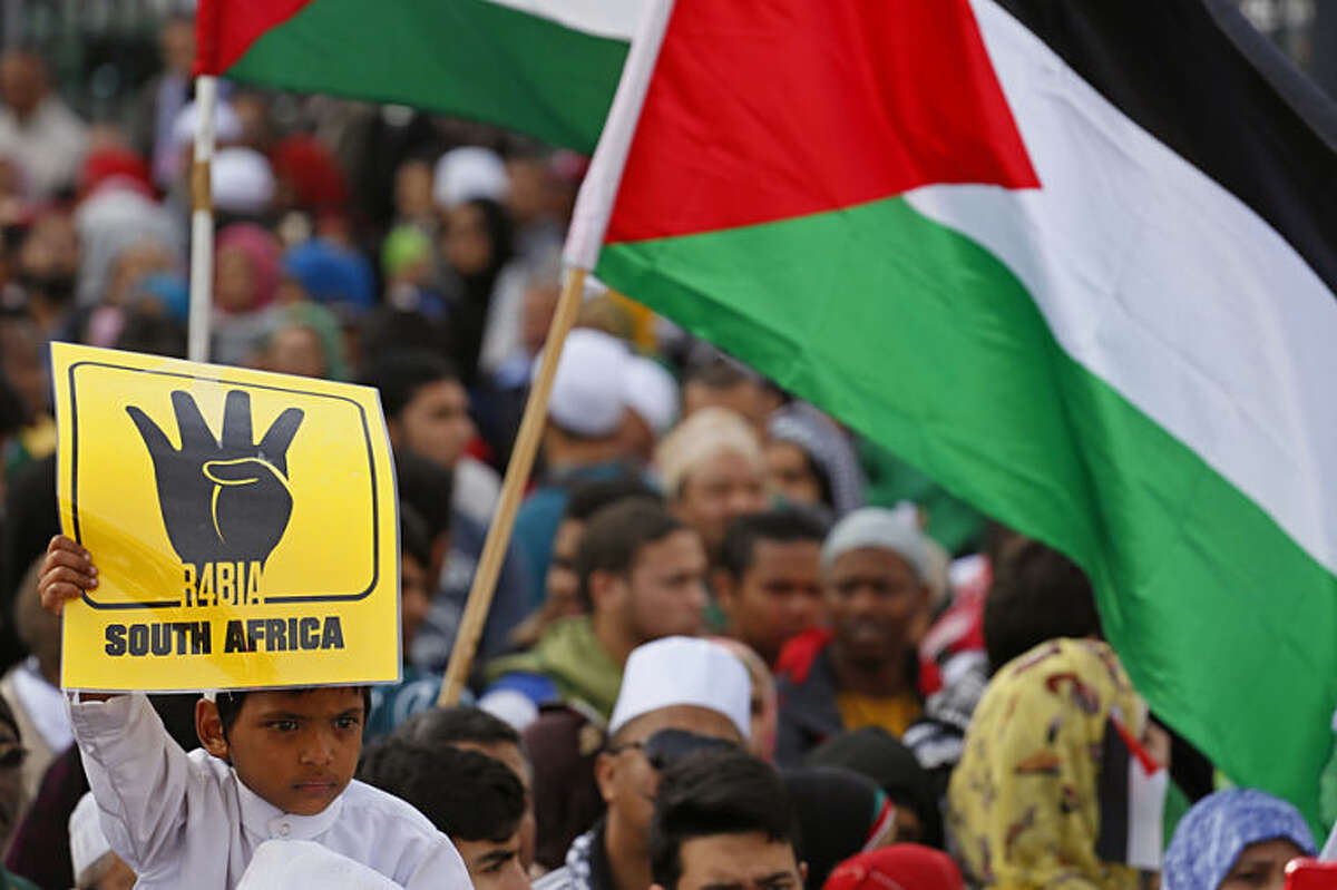 A young boy holds up a symbol of the Muslim Brotherhood as Palestinian supporters take part in a rally against the Israeli occupation of the Palestinian territories in Cape Town, South Africa, Wednesday, July 16, 2014. Thousands of anti-Israel protestors took to the streets marching on the South African parliament building to protest against Israeli occupation and strikes on Gaza. (AP Photo/Schalk van Zuydam)