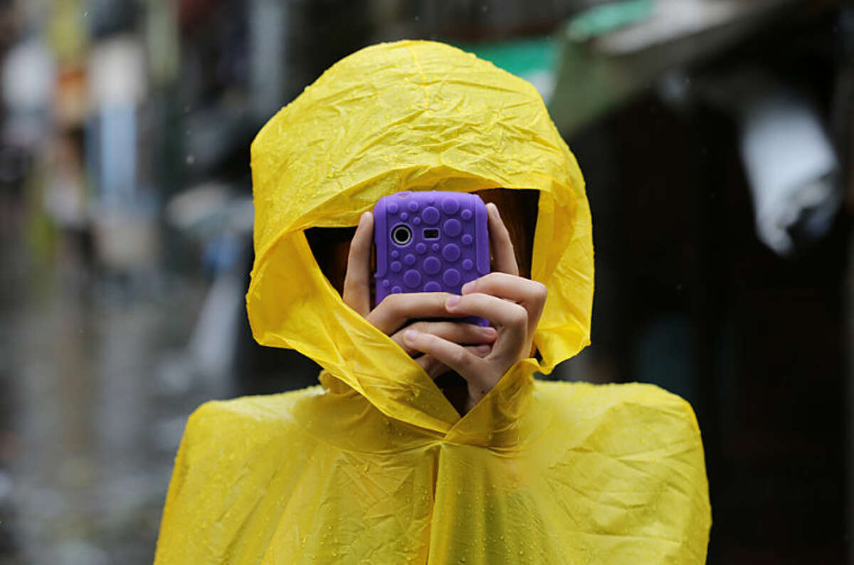 A Filipino resident takes pictures using her smartphone outside a flooded village as Typhoon Rammasun batters suburban Quezon city, north of Manila, Philippines on Wednesday, July 16, 2014. Typhoon Rammasun knocked out power in many areas but it spared the Philippine capital, Manila, and densely-populated northern provinces from being directly battered Wednesday when its fierce wind shifted slightly away, officials said. (AP Photo/Aaron Favila)