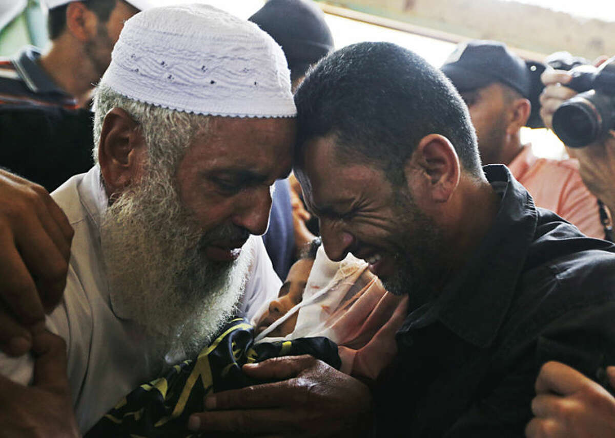 Relatives weep as they hold the body of Sarah Omar el-Eid, 4, as the bodies of her father, Omar, 26, and her uncle, Jihad, 27, are brought into a house in Rafah, southern Gaza Strip, during their funeral, Tuesday, July 15, 2014. The three were killed by an Israeli strike late Monday. Egypt presented a cease-fire plan Monday to end a week of heavy fighting between Israel and Hamas militants in the Gaza Strip that has left at least 185 people dead, and both sides said they were seriously considering the proposal. (AP Photo/Lefteris Pitarakis)