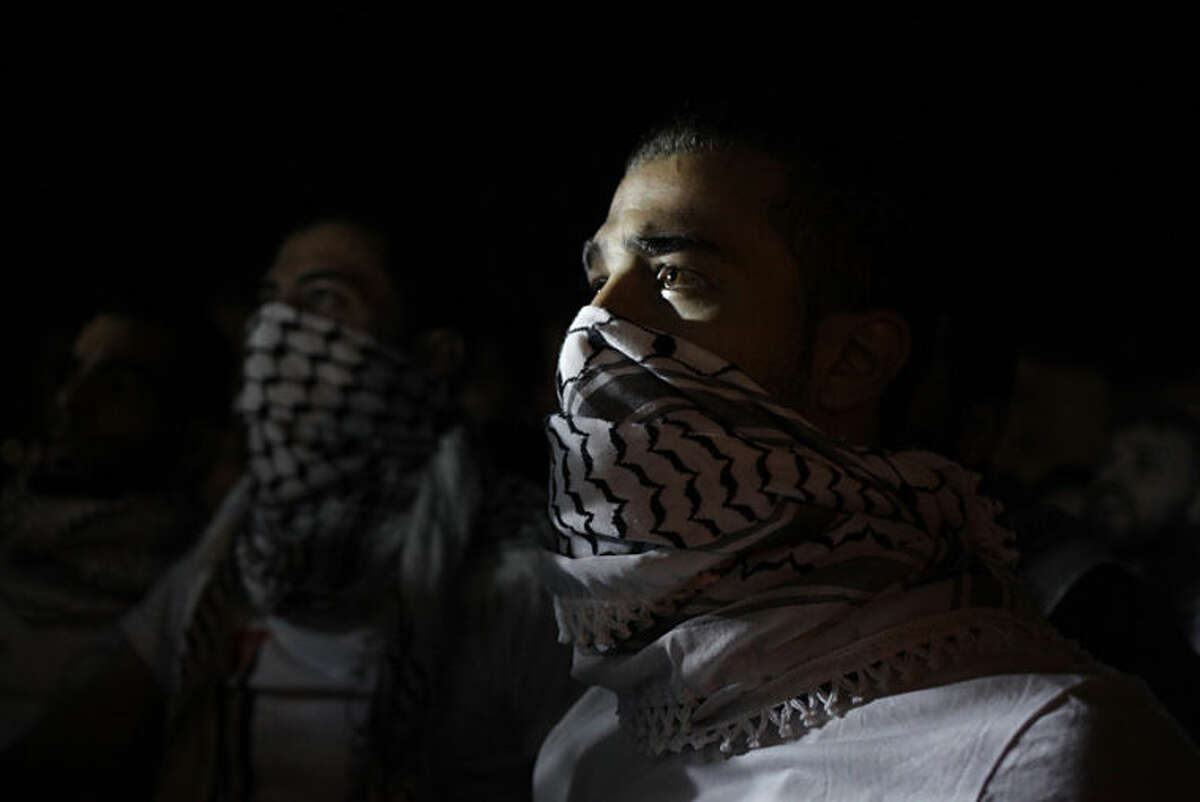 Followers of the Muslim Brotherhood Islamic movement, protest in front of the Israeli embassy to condemn the Israeli bombing of Gaza and to demand that Hamas leaders not accept the truce with the Israelis, in Amman, Jordan, Tuesday, July 15, 2014. (AP Photo/Mohammad Hannon)