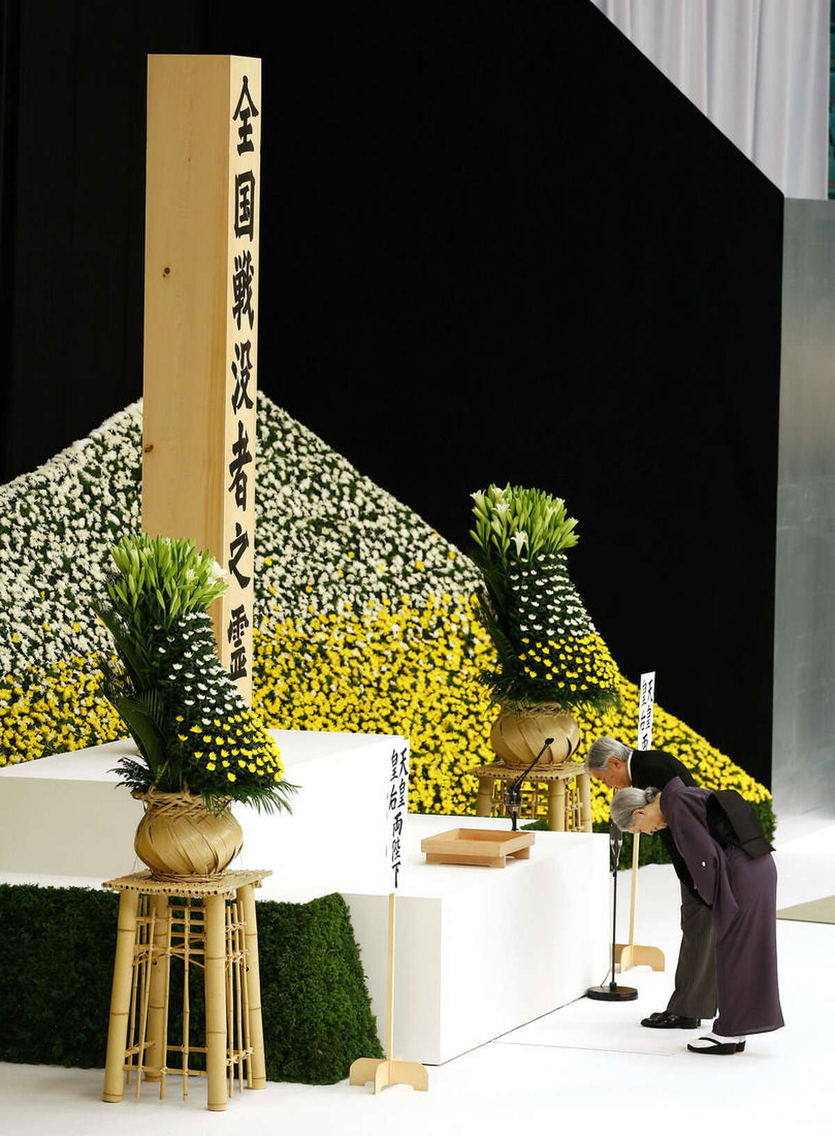 Japan's Emperor Akihito and Empress Michiko bow before the main altar decorated with huge bank of chrysanthemums during a memorial service at Nippon Budokan martial arts hall in Tokyo, Saturday, Aug. 15, 2015. Japan marked Saturday the 70th anniversary of the end of World War II. (AP Photo/Shizuo Kambayashi)