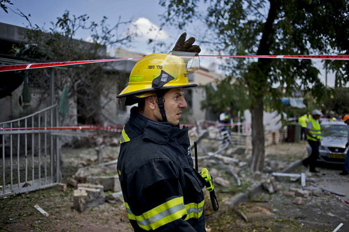 An Israeli firefighter inspects the site after a rocket fired by militants hit Ashdod, Israel, Tuesday, July 15, 2014. Israeli Prime Minister Benjamin Netanyahu warns Hamas that Israel will intensify its week-long campaign against Gaza militants if Hamas rejects an Egyptian-proposed cease-fire. The truce was supposed to go into effect early on Tuesday morning but the Israeli military says 24 rockets have been fired at Israel from the Hamas-controlled Gaza Strip since the expected start of the cease-fire. (AP Photo/Ariel Schalit)