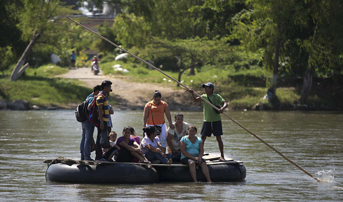 In this Friday, July 11, 2014 photo, people are rafted to the Mexican shore, across the Suchiate river that separates Tecun Uman, Guatemala and Ciudad Hidalgo, Mexico, on a makeshift raft made ??from inner tubes of trucks attached to wooden boards. Scores of Central Americans pay a modest fee crossing the river on these improvised rafts. Mexican politicians generally see little upside in cracking down on migrants who simply want to pass through on the way to the U.S., just like so many Mexicans have done. (AP Photo/Eduardo Verdugo)