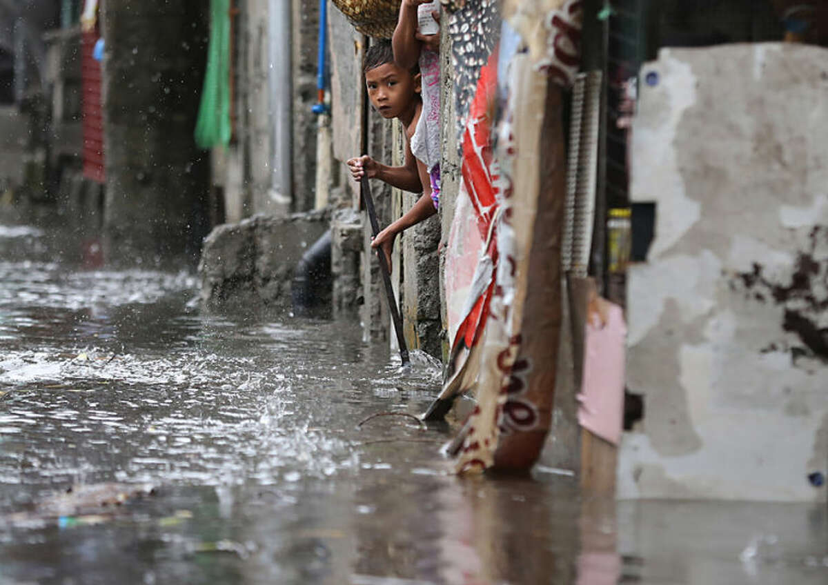 A Filipino boy tries to sweep out floating debris from their flooded home as Typhoon Rammasun batters suburban Quezon city, north of Manila, Philippines on Wednesday, July 16, 2014. Typhoon Rammasun knocked out power in many areas but it spared the Philippine capital, Manila, and densely-populated northern provinces from being directly battered Wednesday when its fierce wind shifted slightly away, officials said. (AP Photo/Aaron Favila)