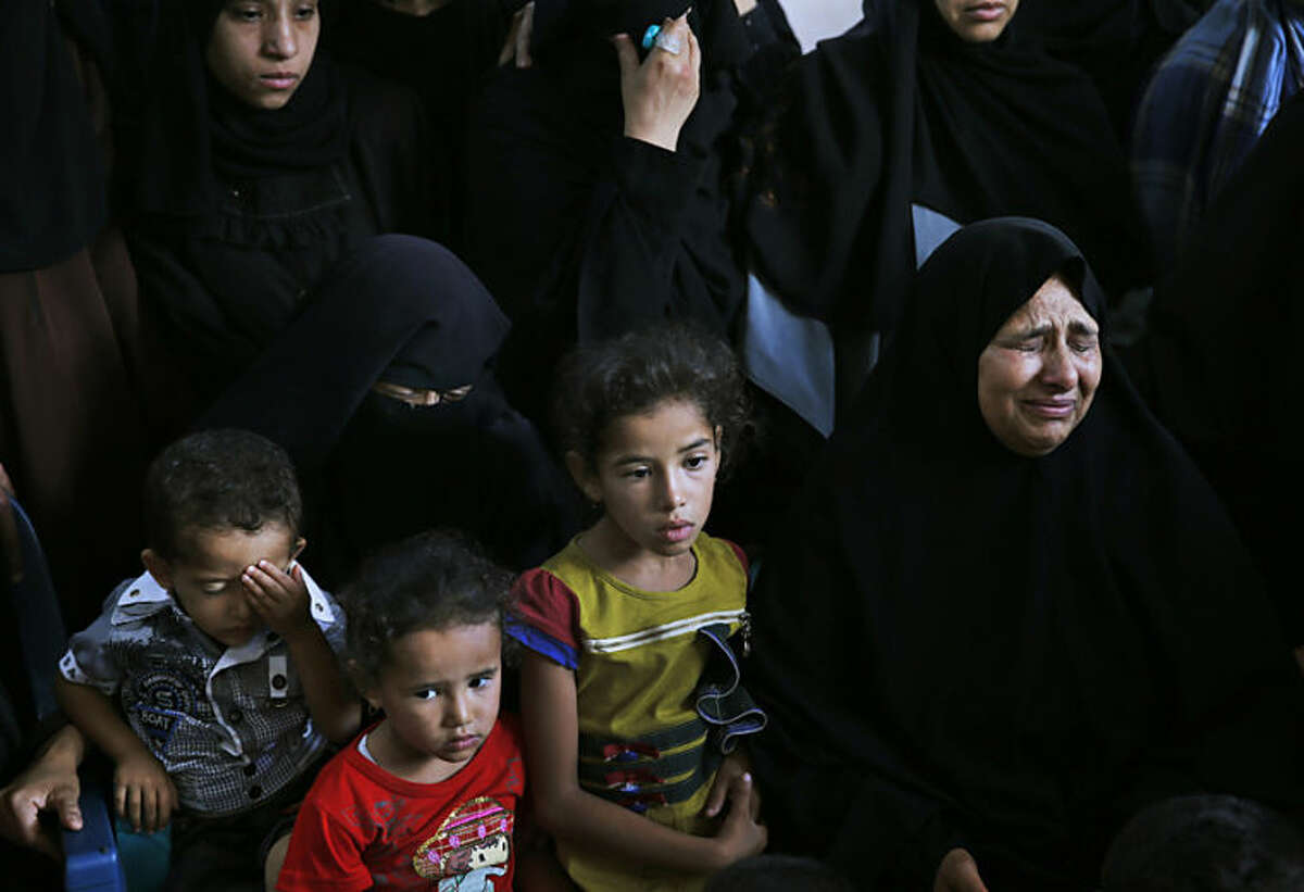 Palestinian Zahra Sheikh el-Eid, right, cries as she waits for the bodies of her daughter Sarah Omar el-Eid, 4, her husband Omar, 26, and her brother-in-law Jihad, 27, to be brought in a house during their funeral in Rafah, southern Gaza Strip, Tuesday, July 15, 2014. The three were killed by an Israeli strike late Monday. An Egyptian truce proposal for the conflict in Gaza quickly unraveled Tuesday, after the Islamic militant group Hamas rejected the plan. (AP Photo/Lefteris Pitarakis)